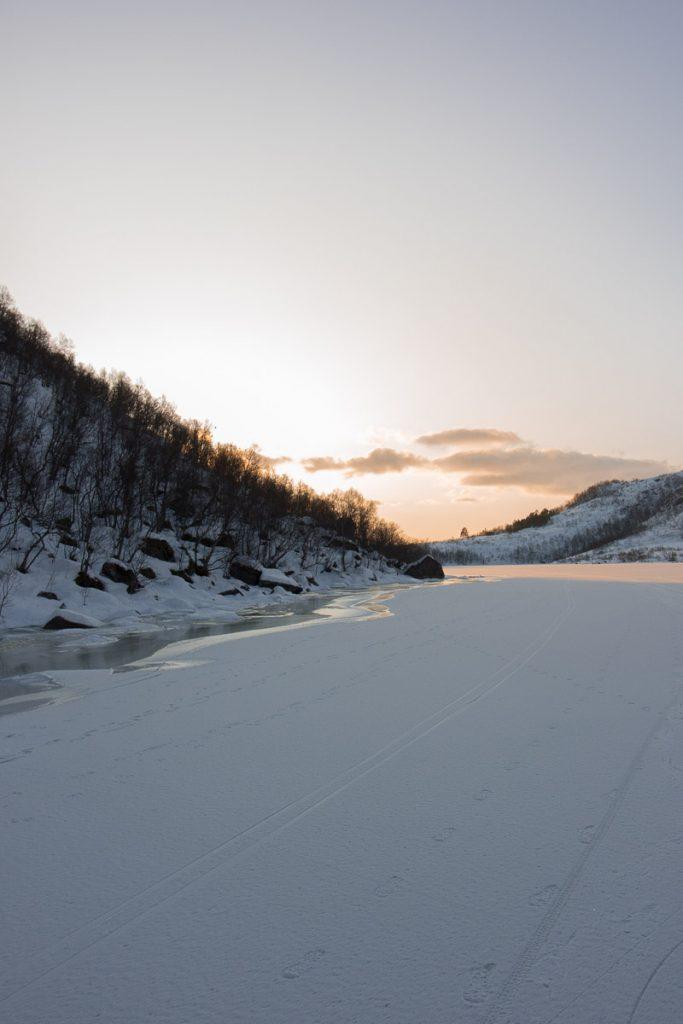 Zonsopkomst vanaf bevroren meer Noorwegen