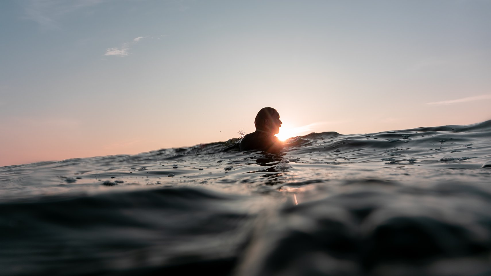 Zonsondergang aan zee met surfer